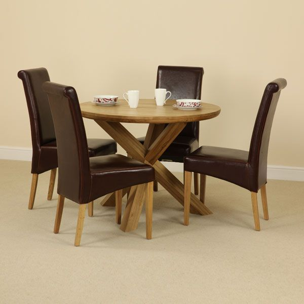 The Solid Oak Round Table With Crossed Legs And Four Brown Scroll Back Chairs