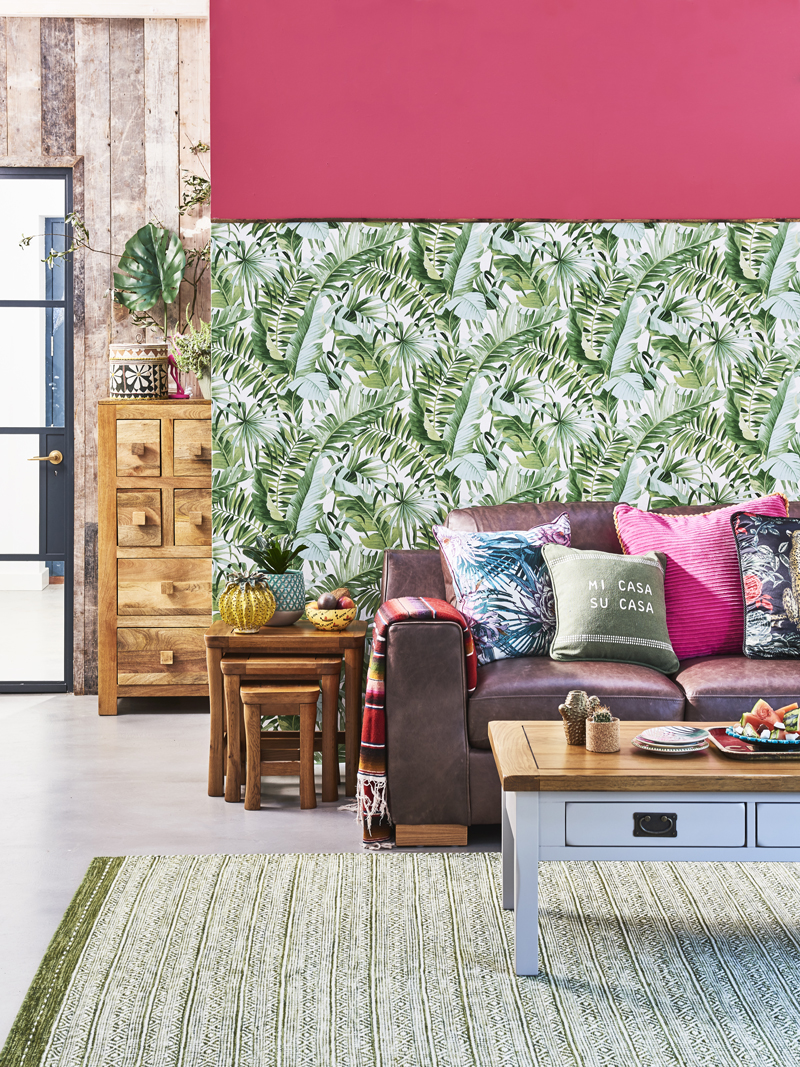 Floral wallpaper contrasting pink wall and sofa with bright accessories