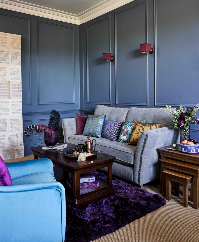 Living room with blue walls and grey studded sofa