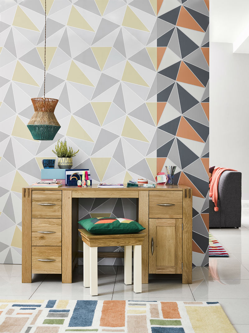 Natural wood office desk with geometric wallpaper feature