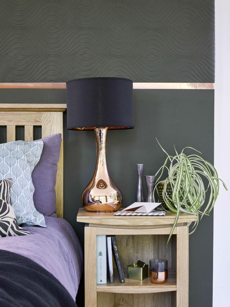 Copper and black lamp on oak bedside table