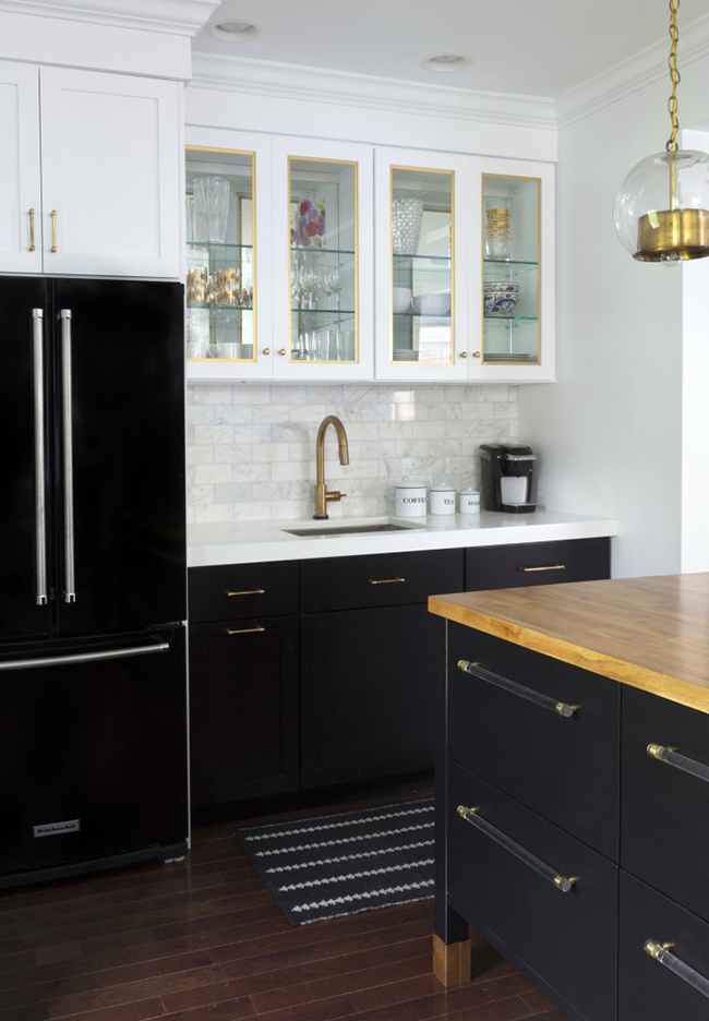 Black-refrigerator-with-black-base-cabinets-and-white-upper-cabinets-marble-subway-tile-brass-hardware-kitchen-