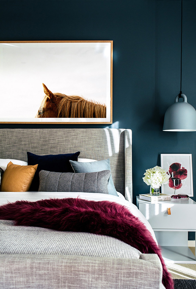 dark bedroom with grey and burgundy bedding