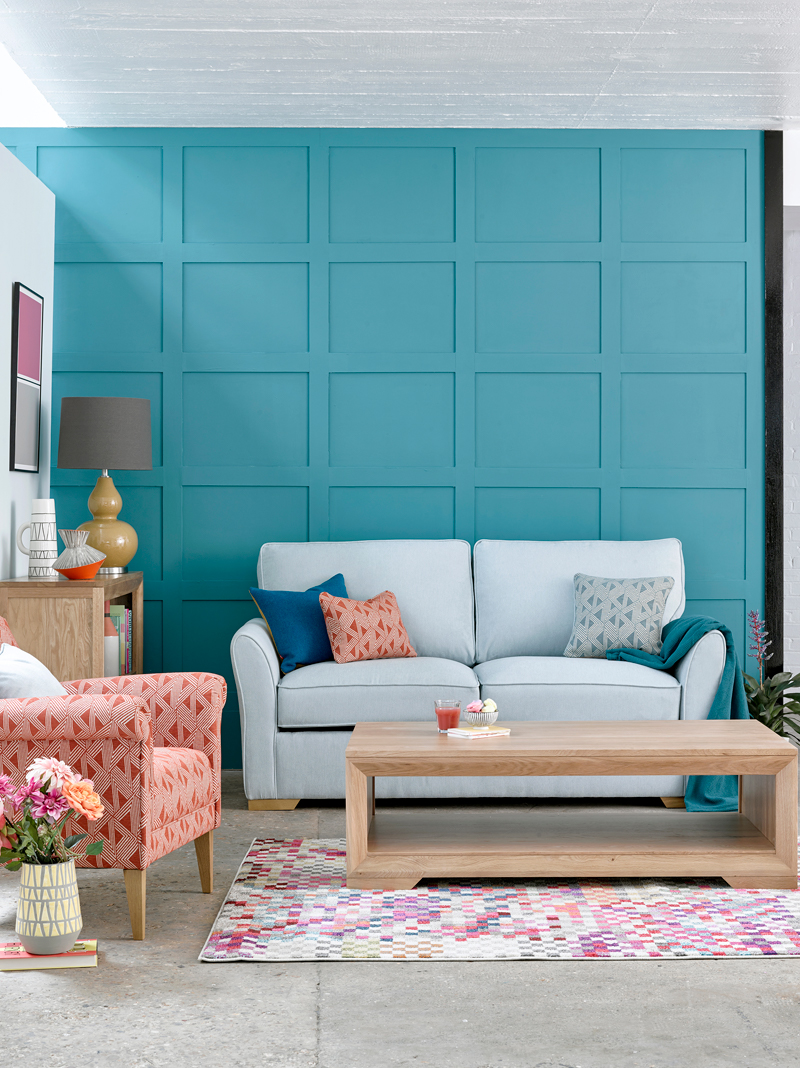 Jasmine Sofa Bed and Red Accent chair against blue panelled wall