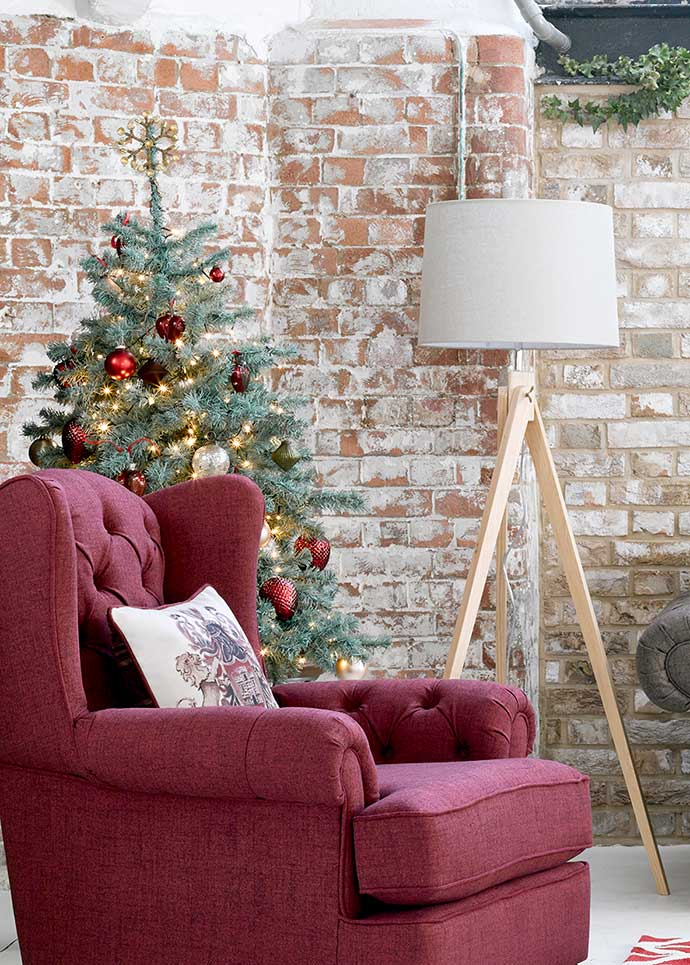christmas tree beside armchair and lamp