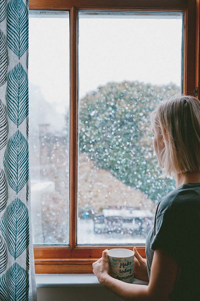 woman stood by window looking outside at snow