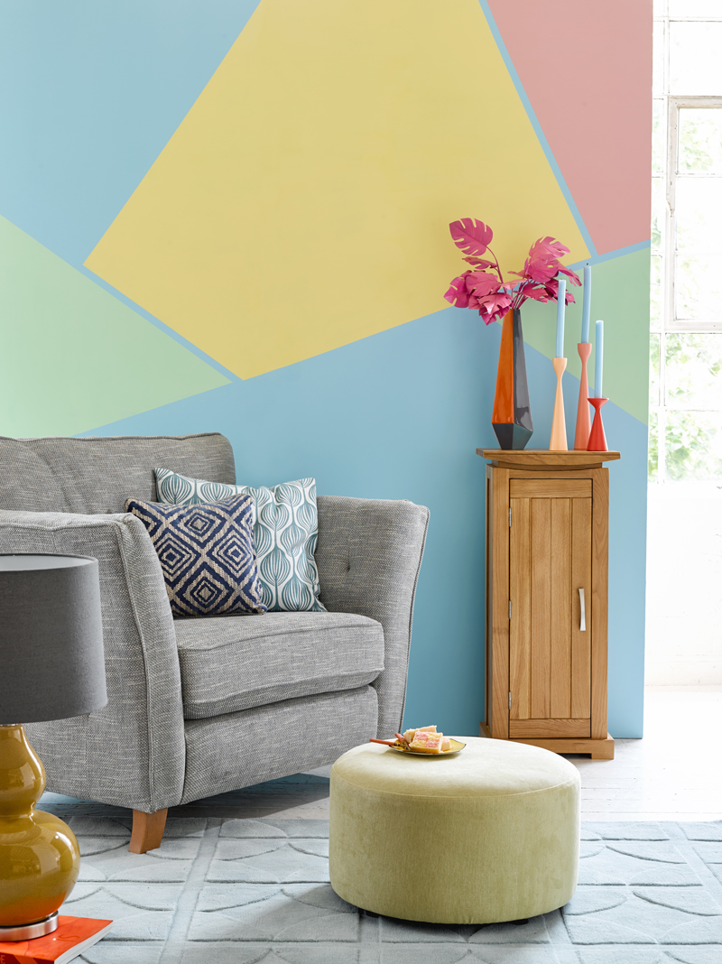 Grey armchair against a sorbet geometric feature wall
