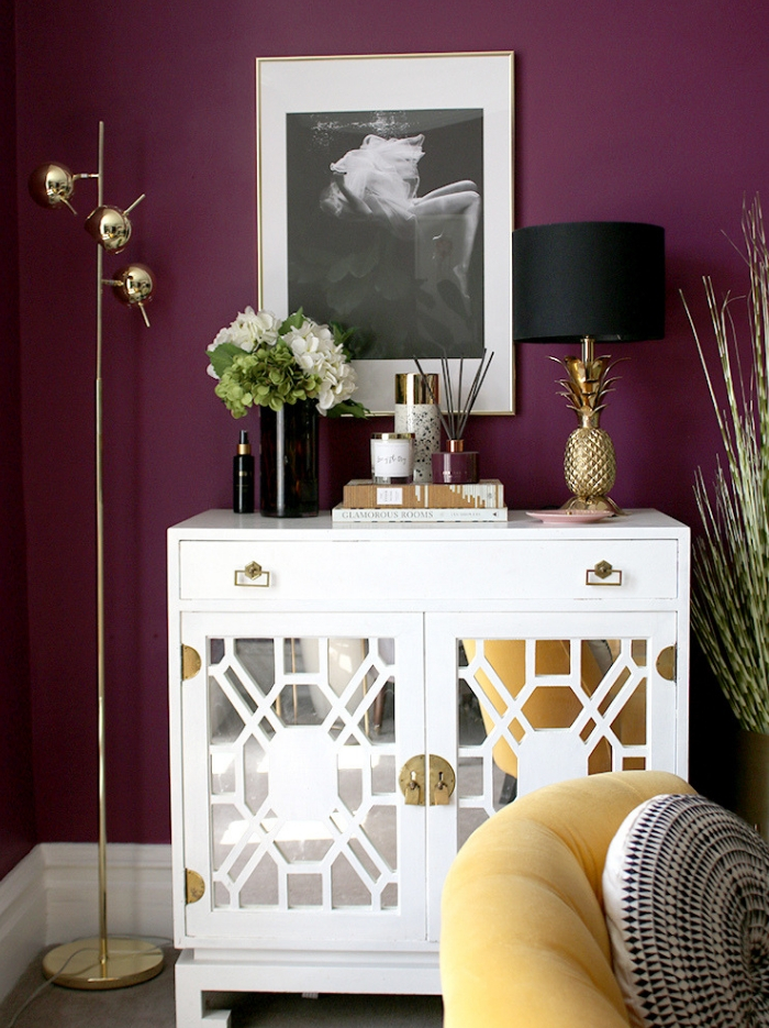 Dark purple walls and bright white sideboard