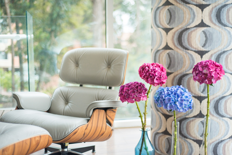 Cream chair, funky wallpaper and flowers