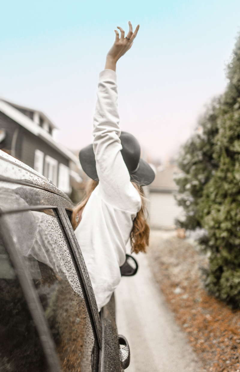 Woman hanging out of car window with her arm up