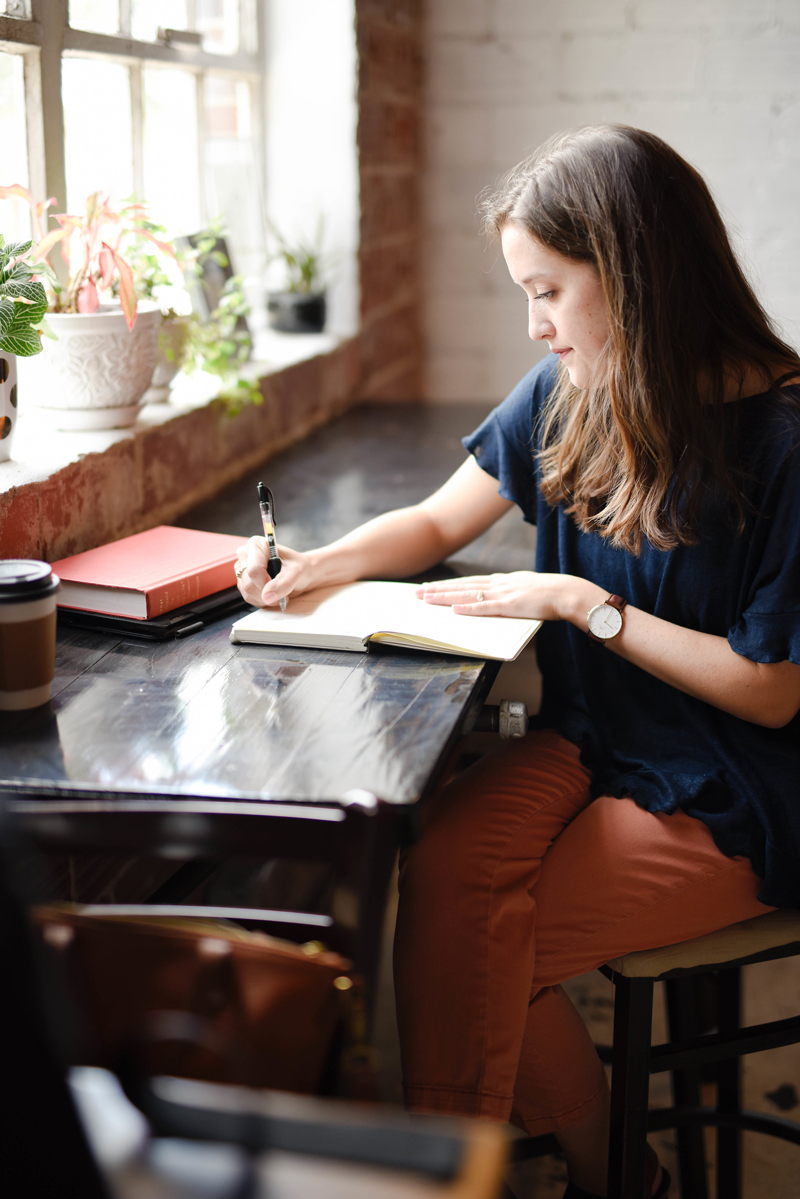 Woman writing at Coffee Shop