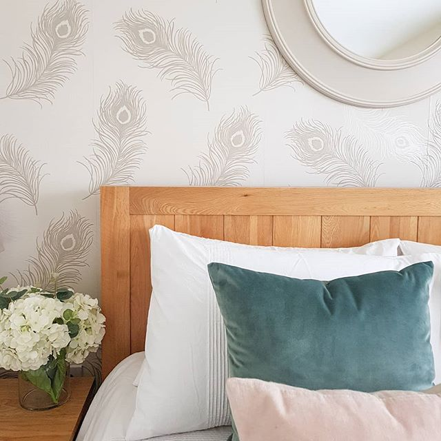Warm bed frame with dusky toned accessories and feather printed wallpaper