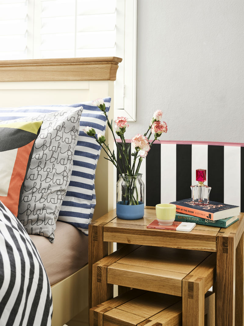 A brightly coloured bedside with a bouquet of flowers in bloom