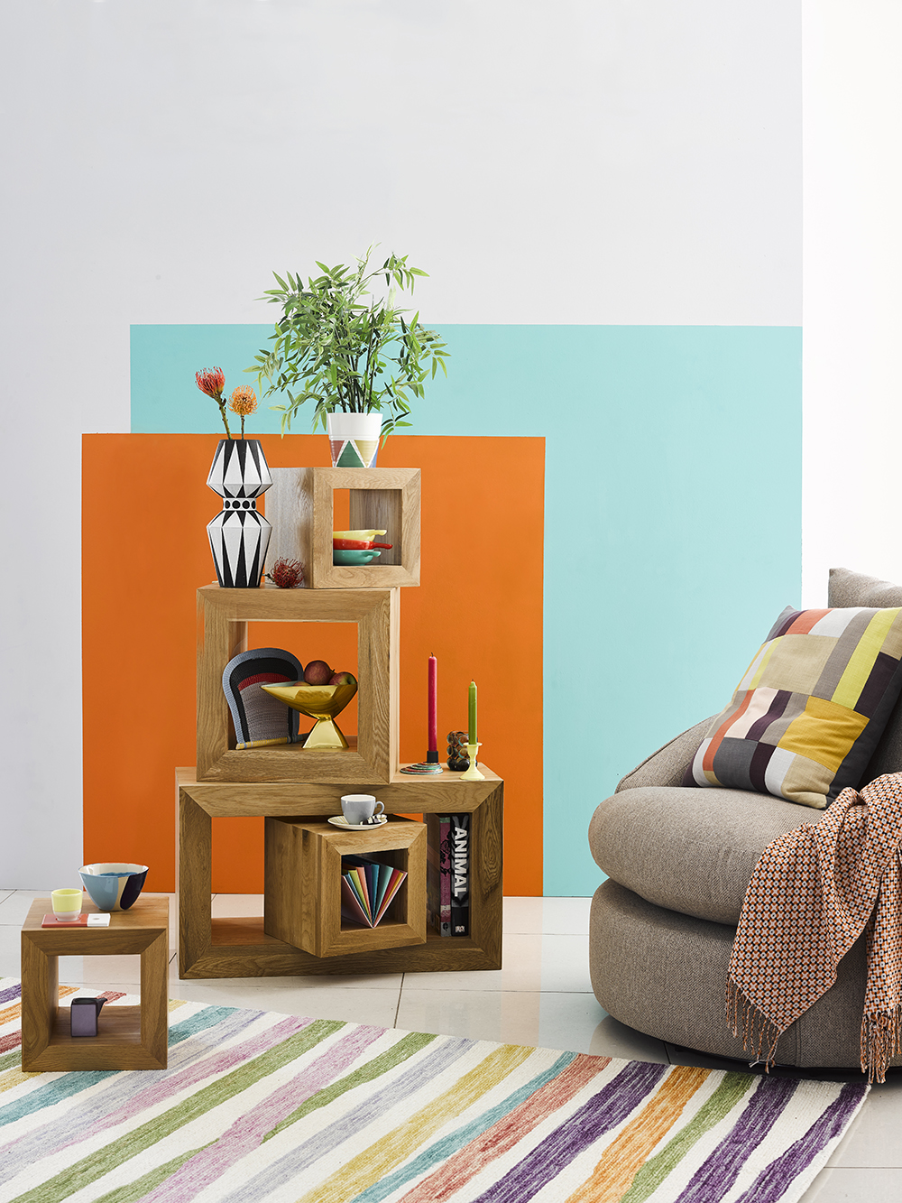 Box shelves and beige armchair blue and orange walls