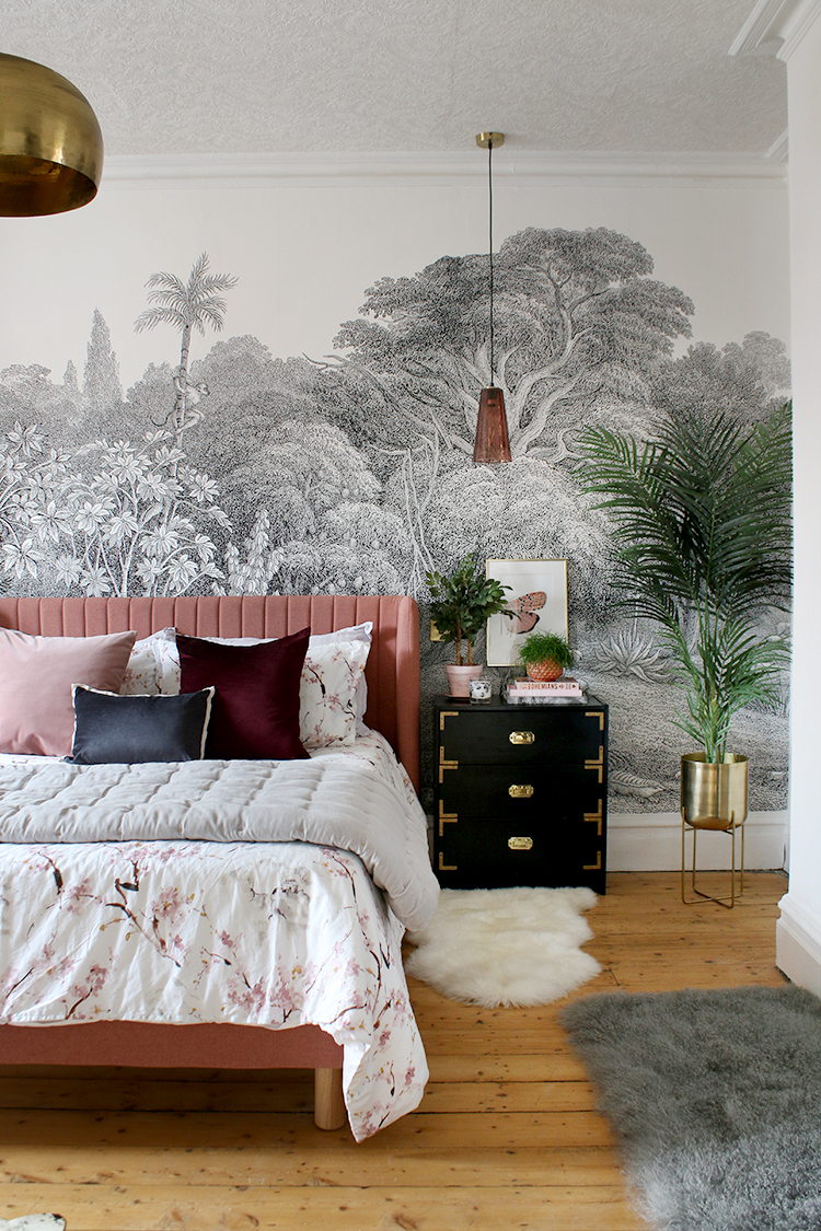 Pink bed in bedroom with ornate wallpaper