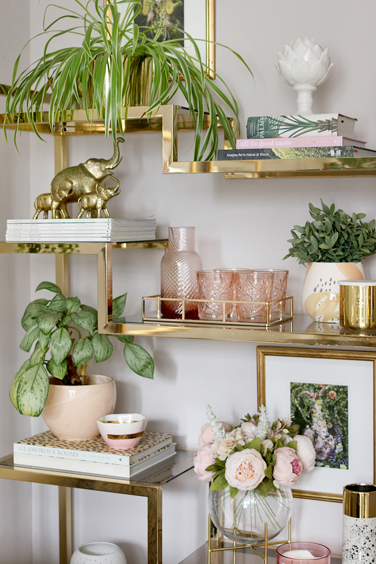 Gold ornate shelving with plants and pink ornaments