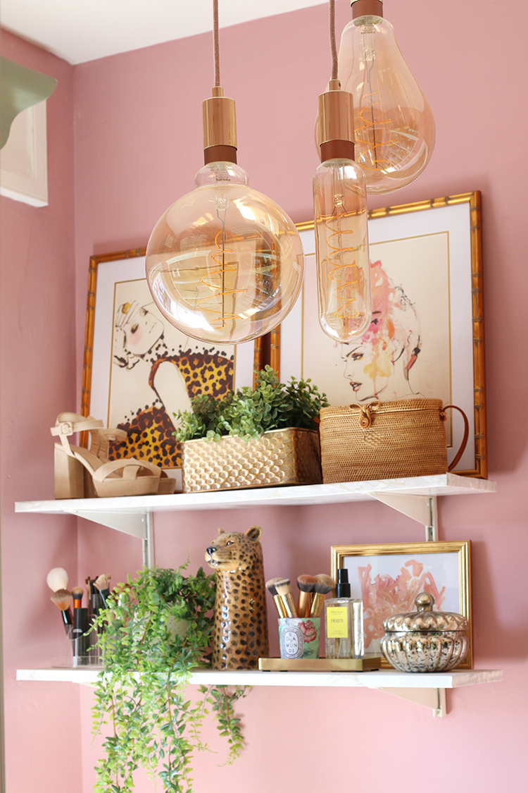 White wall shelving, pink walls and ornate light bulbs