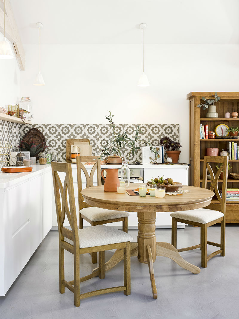 a kitchen with round dining table and bookcase