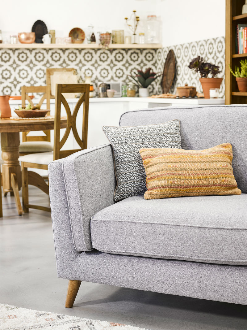 Grey loveseat with terracotta coloured cushion