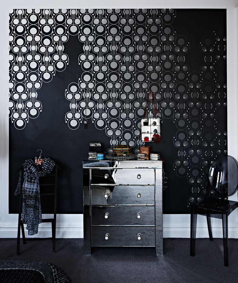 Mirrored chest of drawers and black mosaic bedroom wall