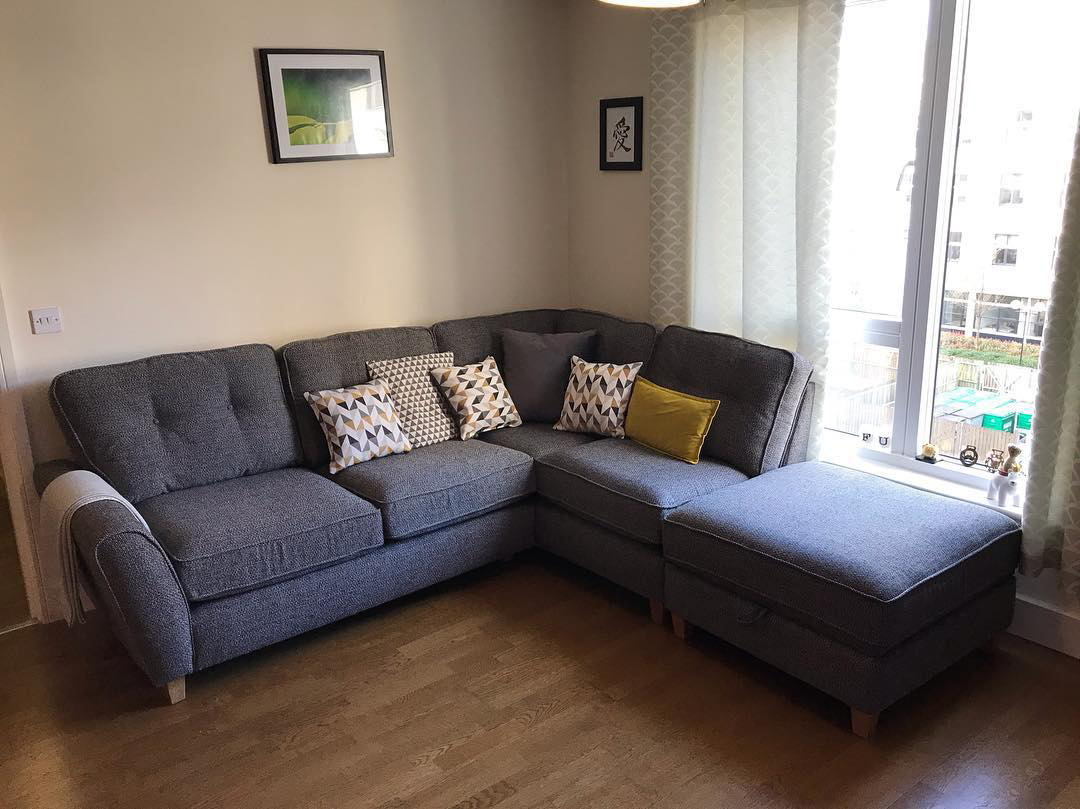 blue corner sofa with mustard cushions