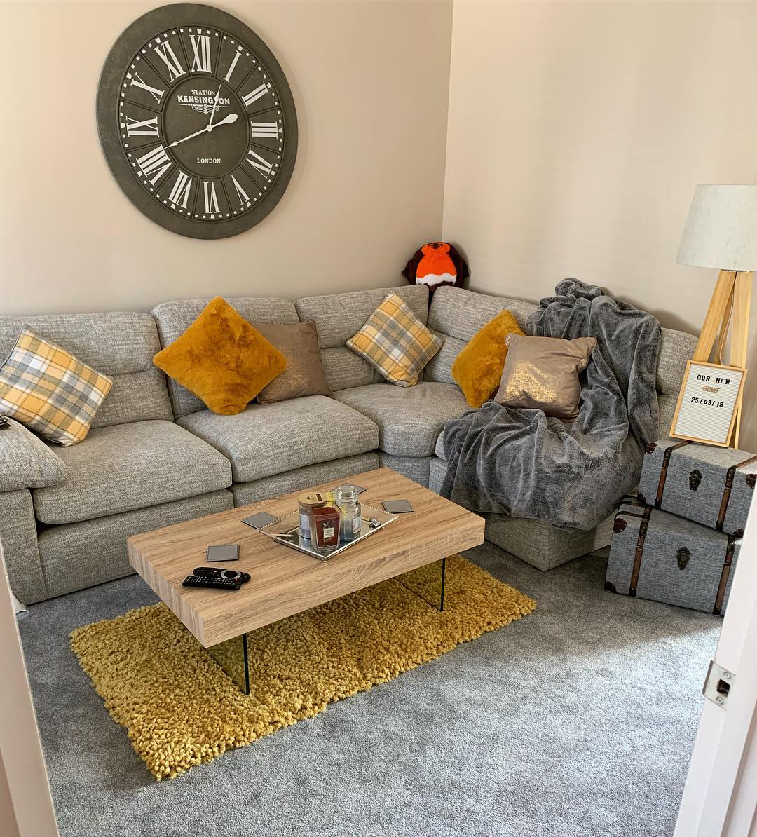 Grey corner sofa with yellow accessories
