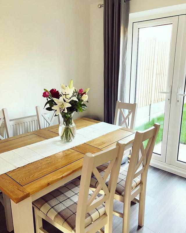 grey painted dining table with flowers and runner