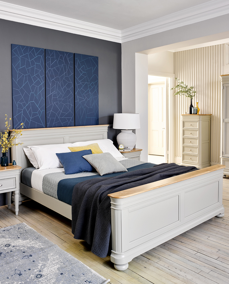 White painted bed in blue bedroom