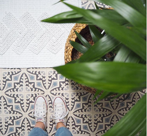 grey mosaic tiled floor with plant and shoes