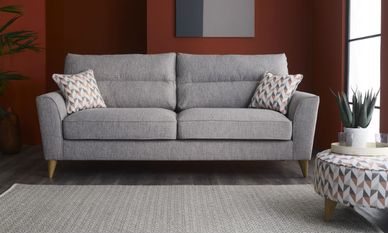 Grey fabric sofa with geometric cushions and matching rug