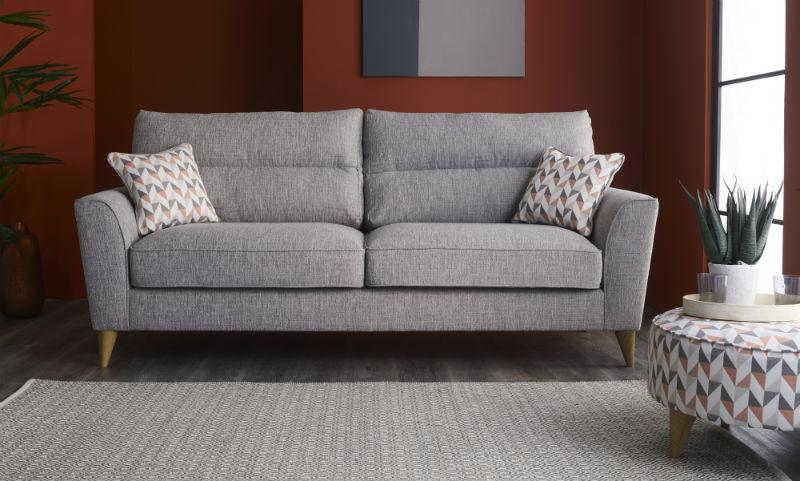 Grey fabric sofa with geometric cushions and matching rug