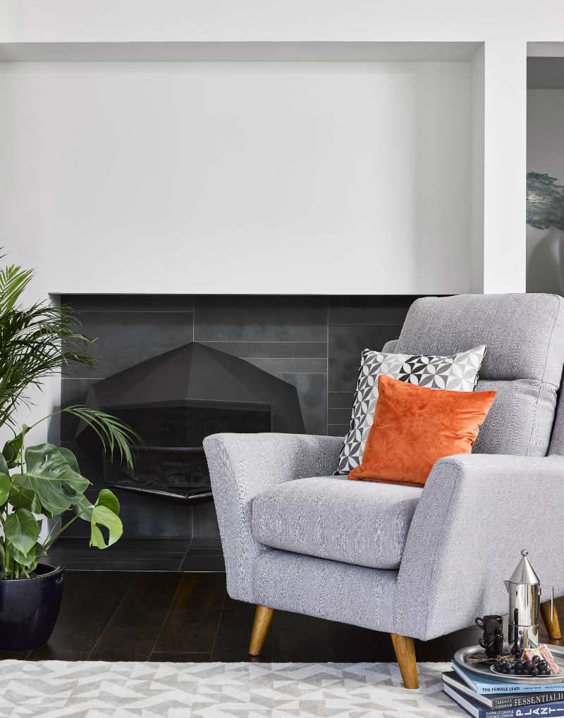 Silver accent chair infront of fire