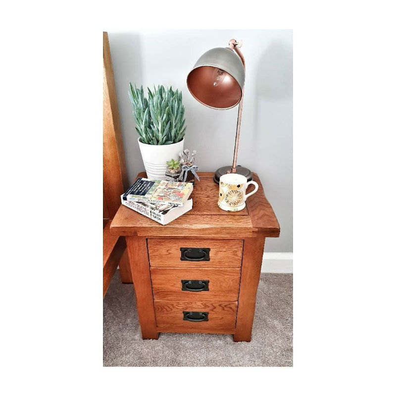 rustic oak bedside table with books and night light