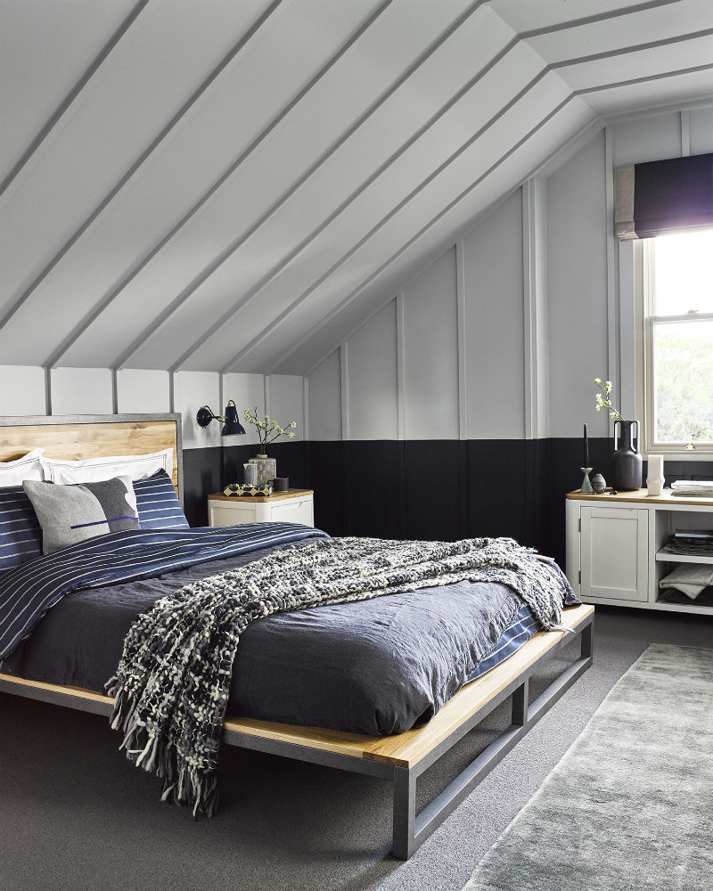 Grey panelled loft conversion bedroom with industrial style bed