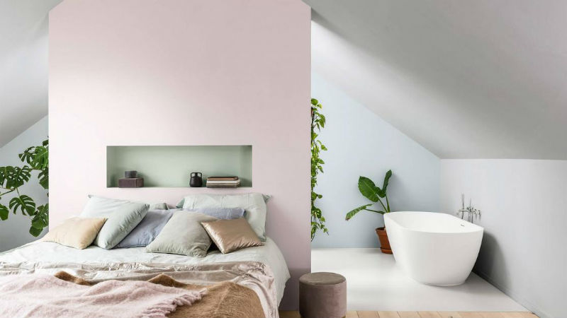 bedroom with pink feature wall and floating bath tub