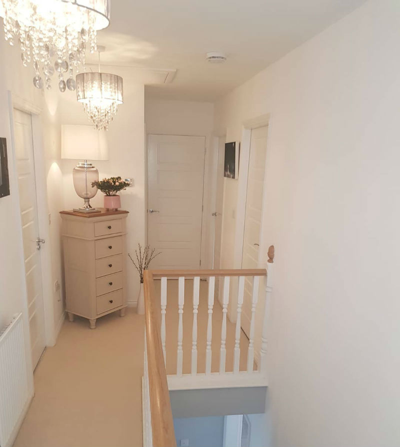 white painted tallboy in light upstairs hallway