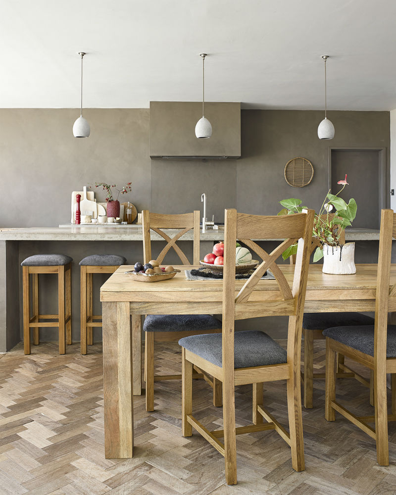 Stylish, refined dining room with a mango wood table and rustic dining chairs and stools
