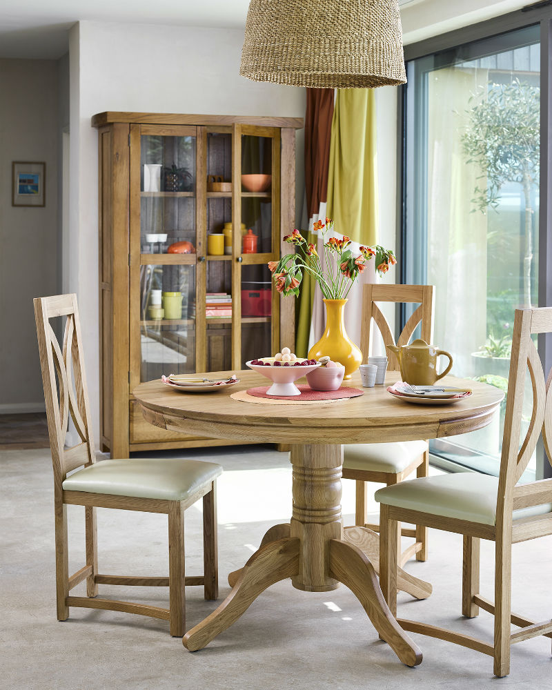 round oak dining table and chairs in rustic dining room