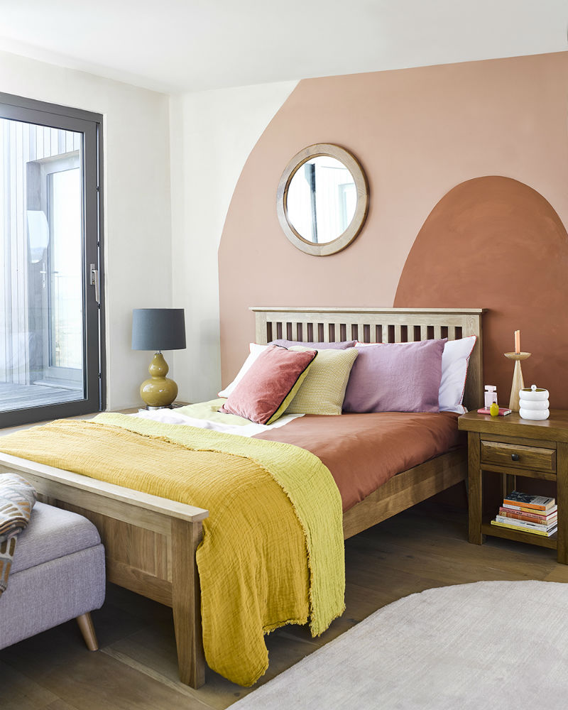 A wide shot of a bedroom with a distinctive and warm feature wall with sunset colours