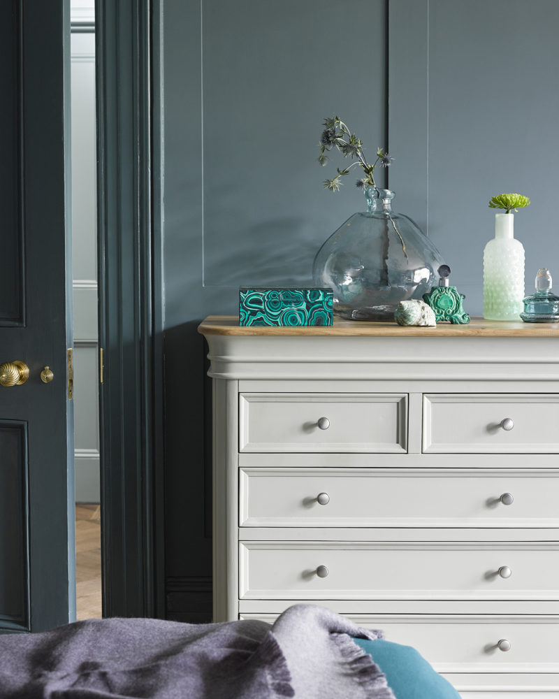 sage green painted chest of drawers in blue toned bedroom