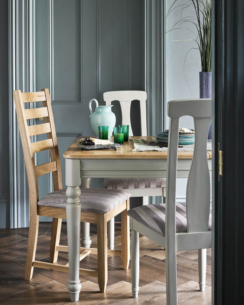 sage green painted dining table and contrasting chairs