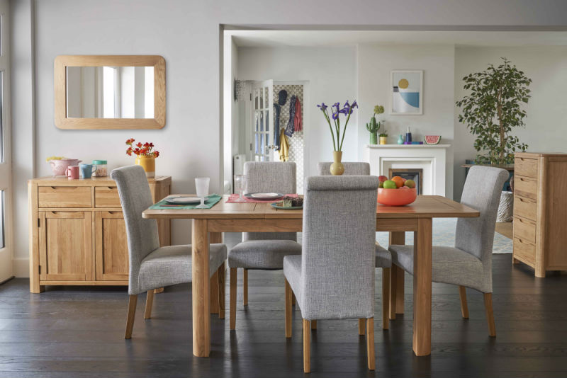 curved oak dining table with grey fabric dining chairs