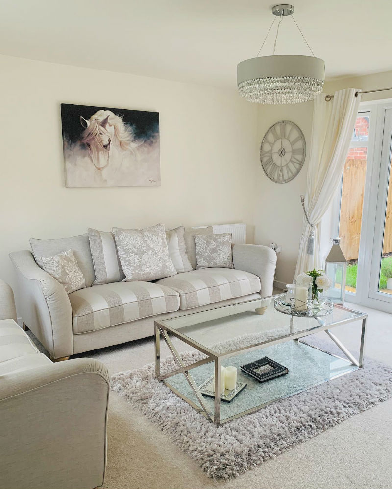 Silver and white striped sofa in neutral living room
