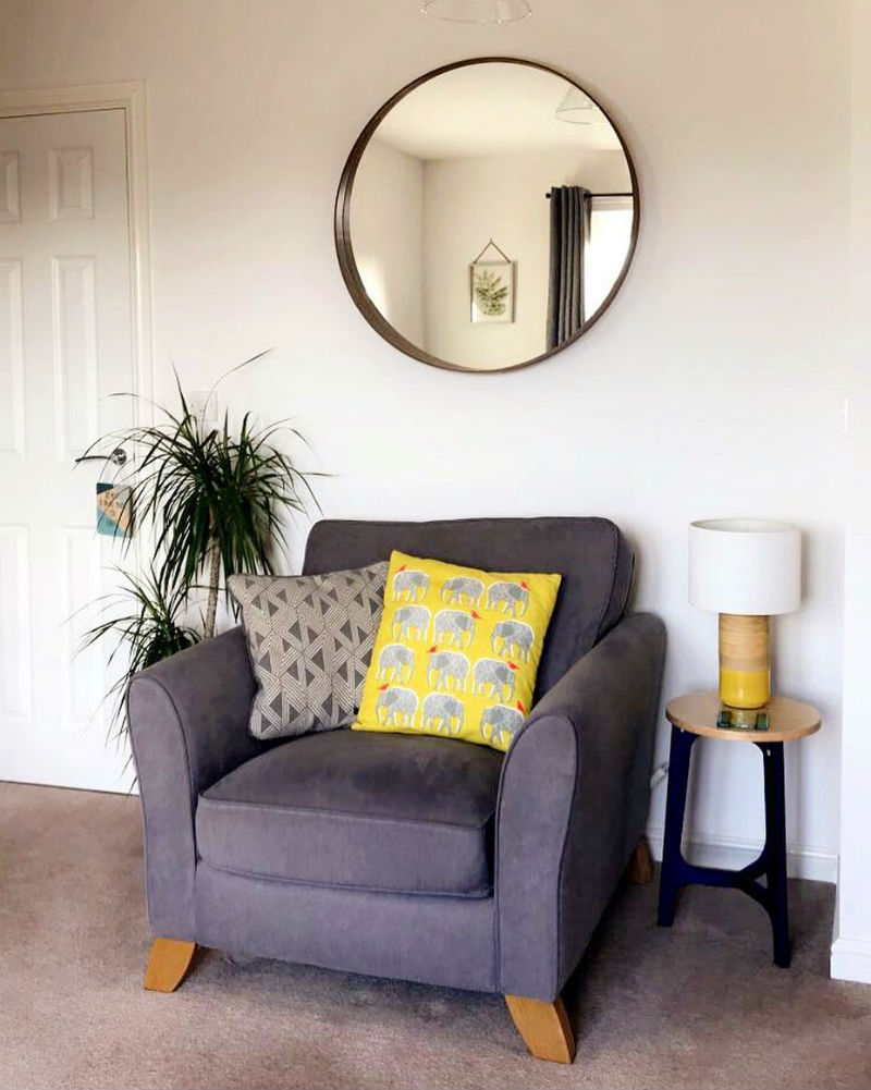 grey loveseat with patterned cushions and plants