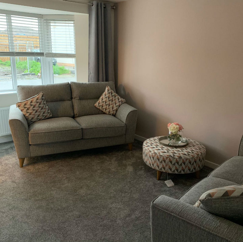 grey sofa and matching footstool with geometric cushions