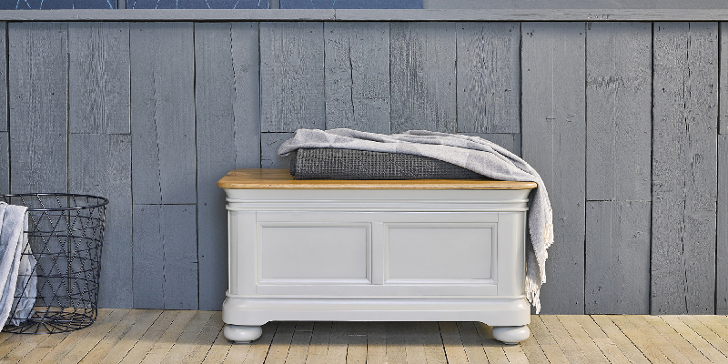 sage green painted blanket box against rustic blue wall