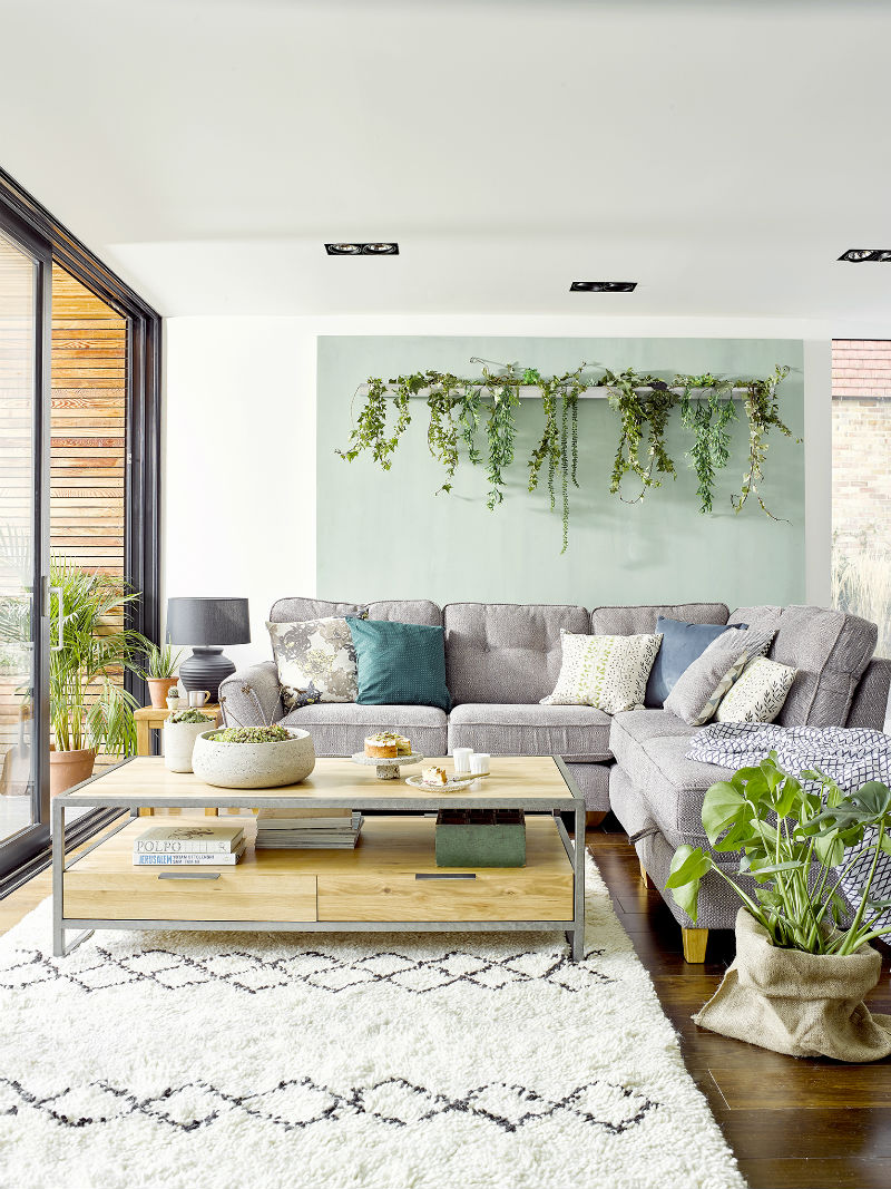 Greenhouse-inspired living room with plenty of houseplants, a grey fabric upholstered corner sofa and industrial-inspired coffee table made from oak and metal