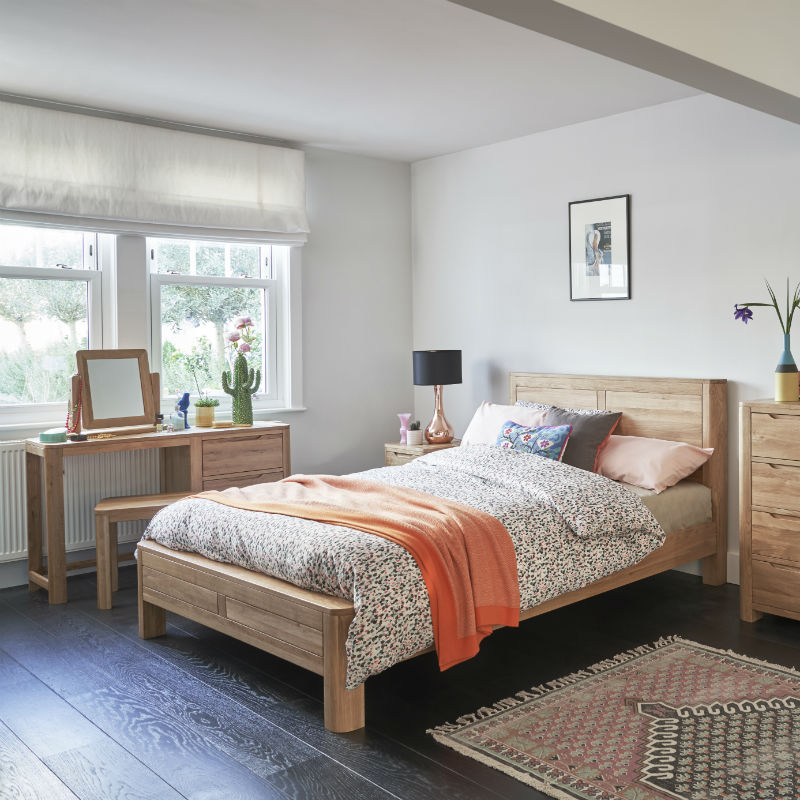 Natural oak king-size bed with rounded edges and geometric detailing in a bedroom with matching furniture including a dressing table set, bedside table and chest of drawers