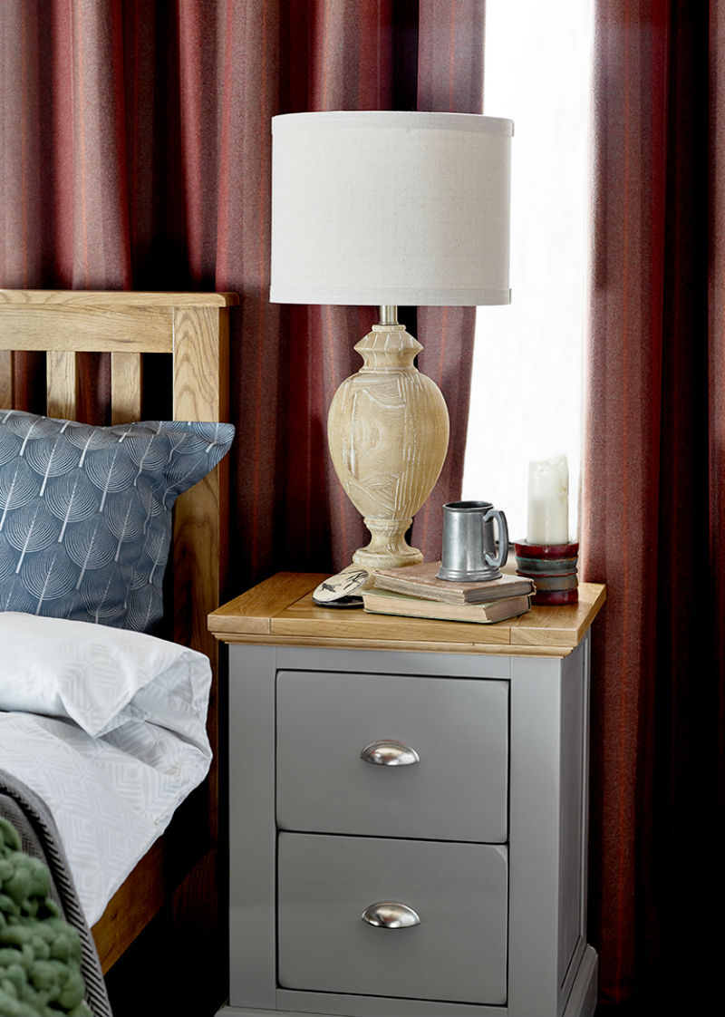 Naturally textured wooden lamp atop grey-painted and oak bedside table with modern metal handles