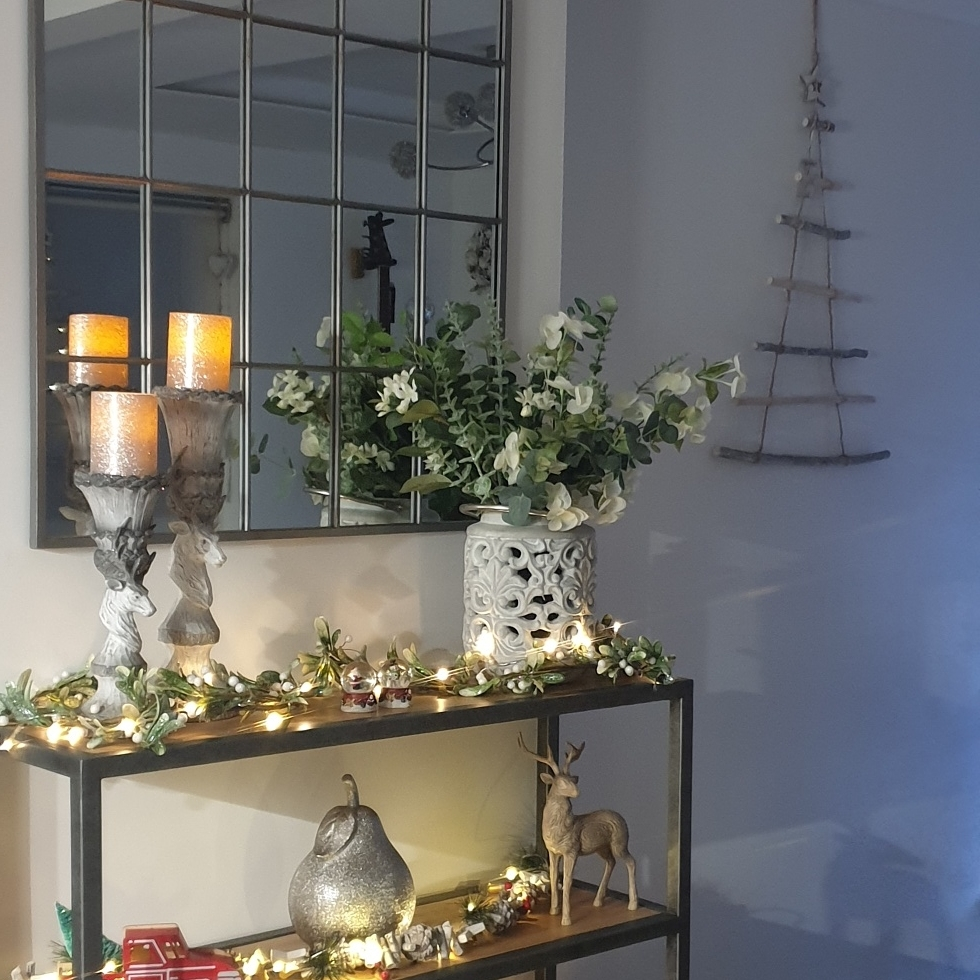 festive bookcase decorated with white and green decorations